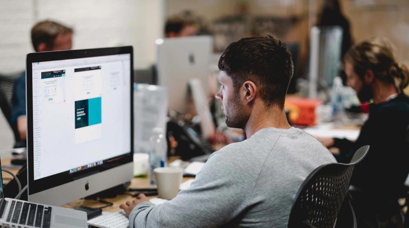 software developer internship: Male employee working on his desktop computer