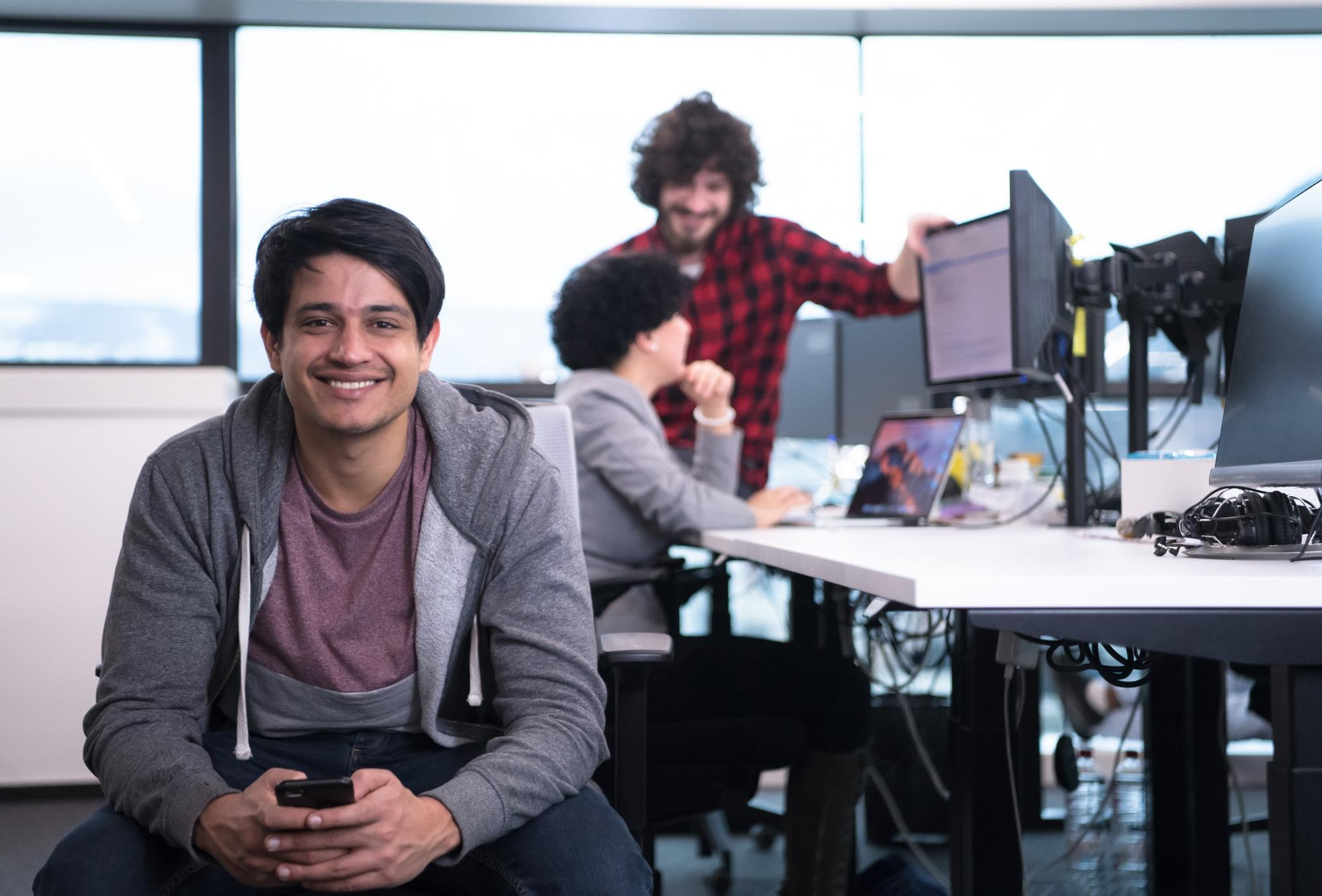 software developer internship: Man holding his mobile phone and smiling at the camera