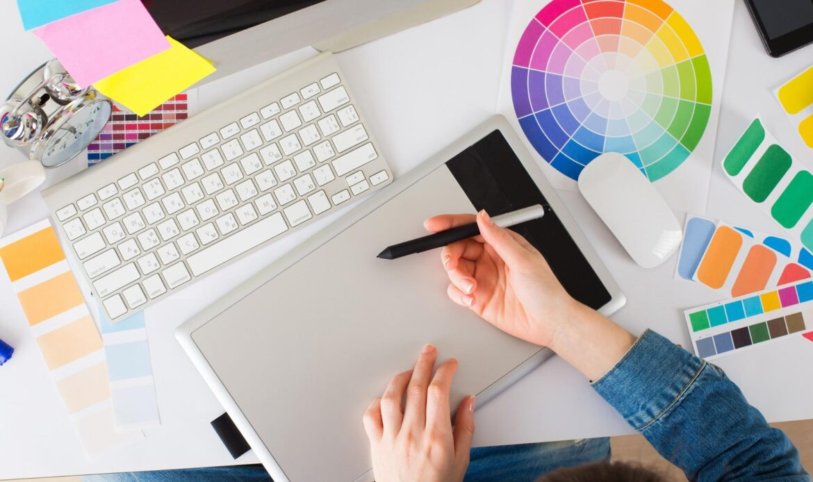 Graphic Design Internship: Intern's hand and other designer tools on a table