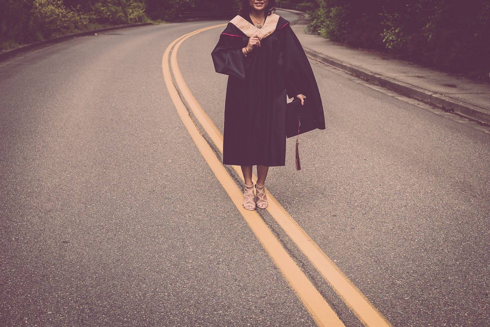 Fellowship vs. Internship: Young woman in graduation cap and gown