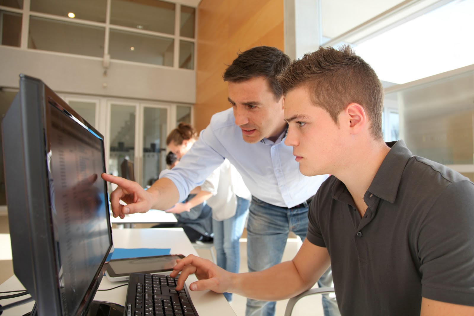 Externship vs. Internship: Two men looking at a computer screen