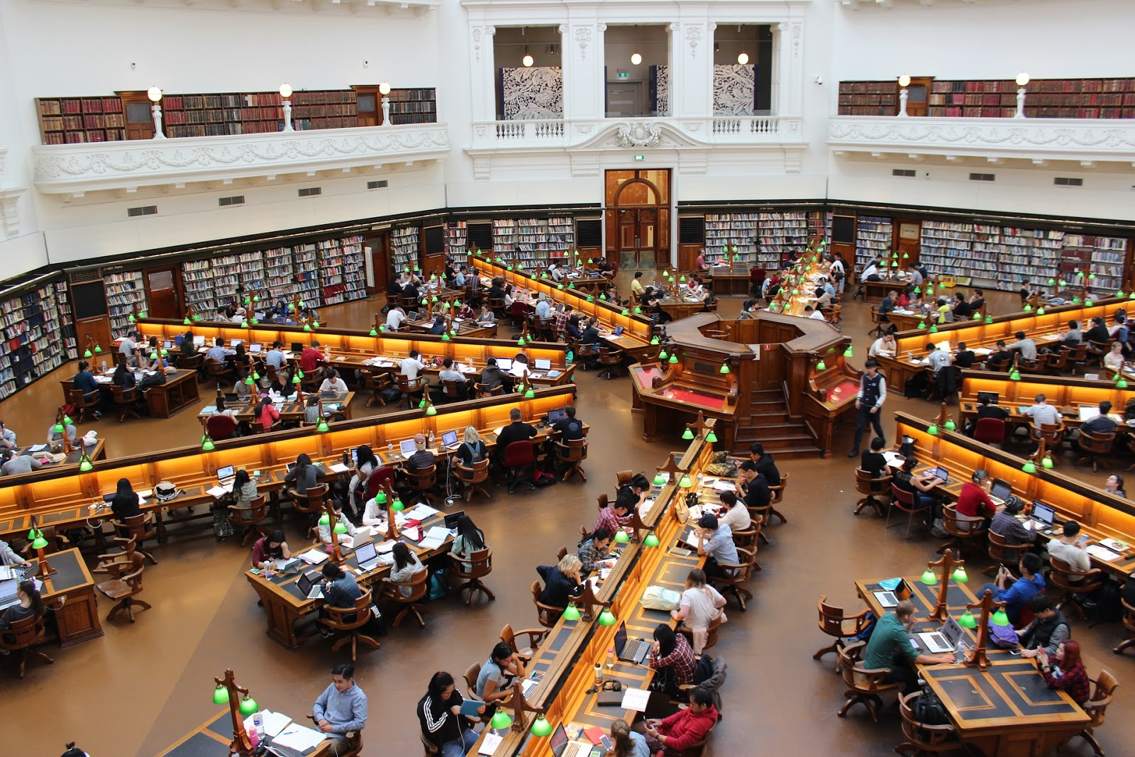 Wide view of an enormous library filled with people