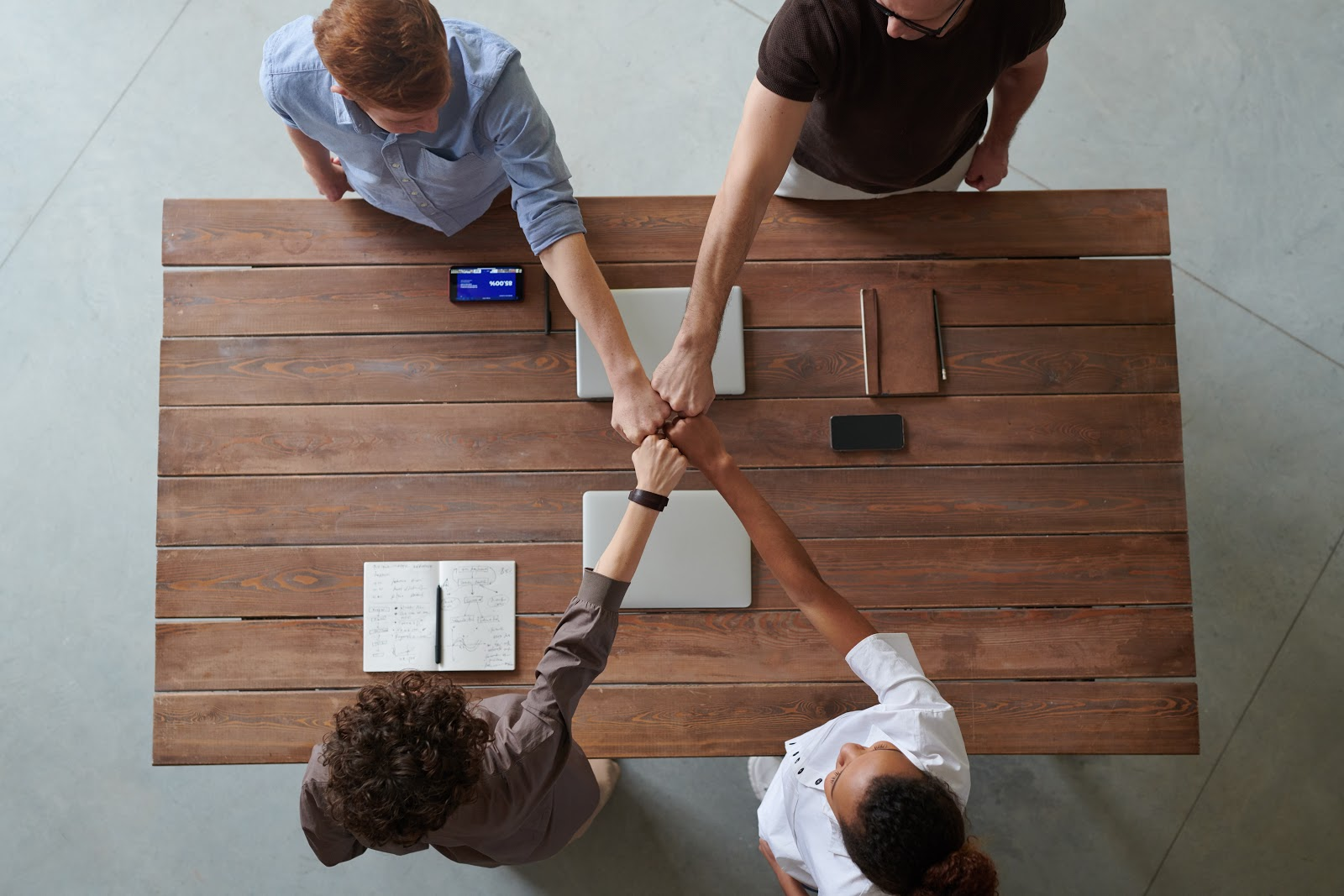 Co-Op vs. Internship: Four people doing fist bump