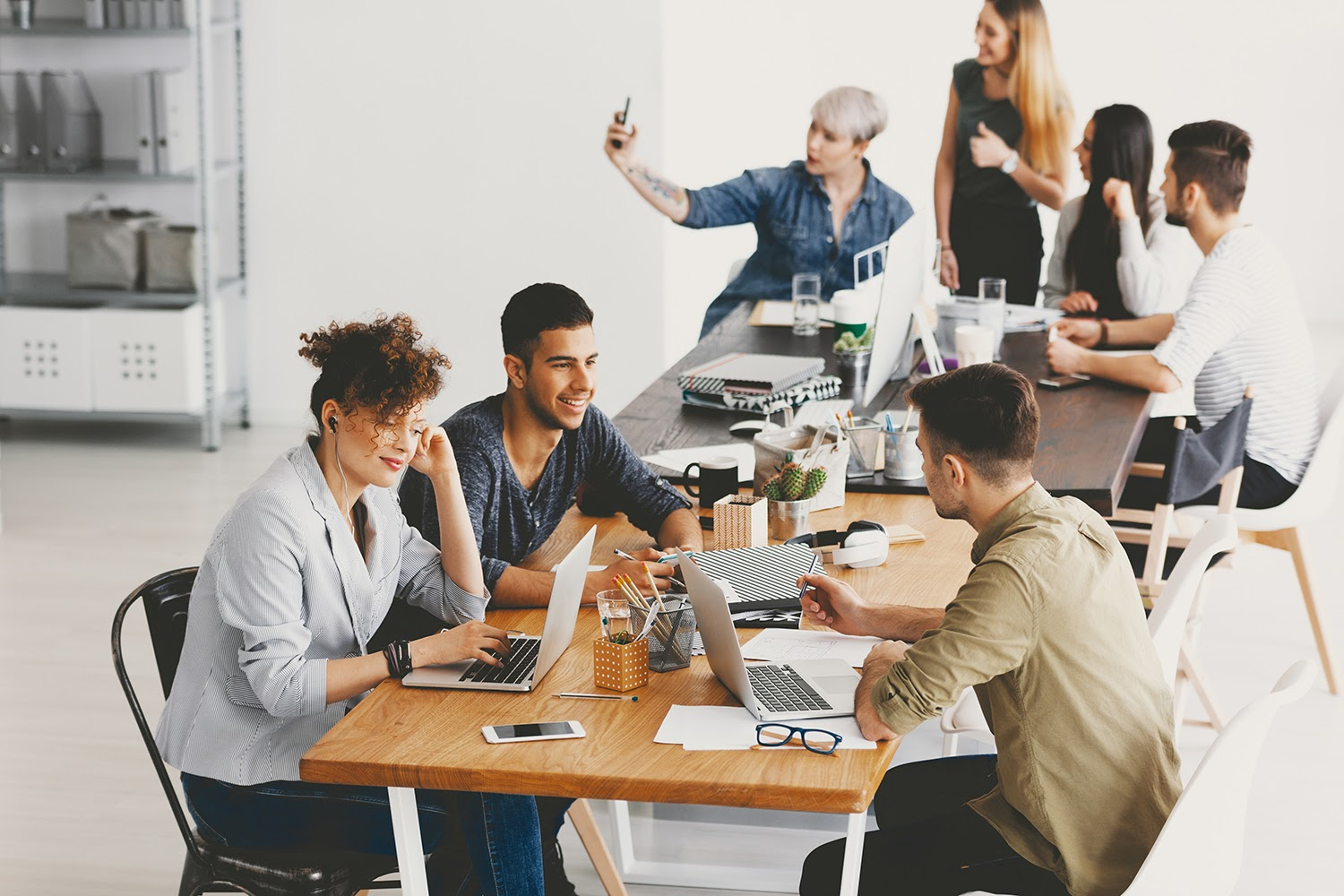Why hire interns: Diverse group of young interns at two different office tables