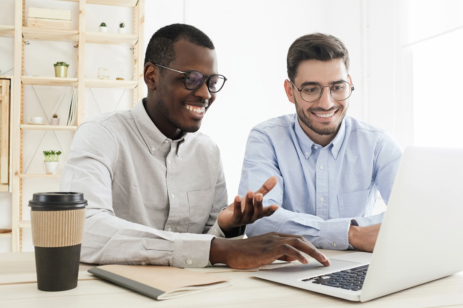 Two young men writing an internship thank you letter on a laptop