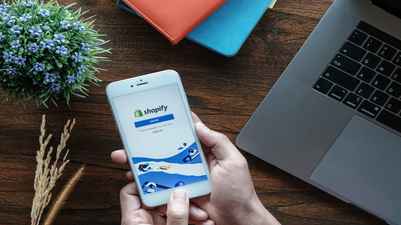 Shopify internship: A hand holds a phone with Shopify on the screen