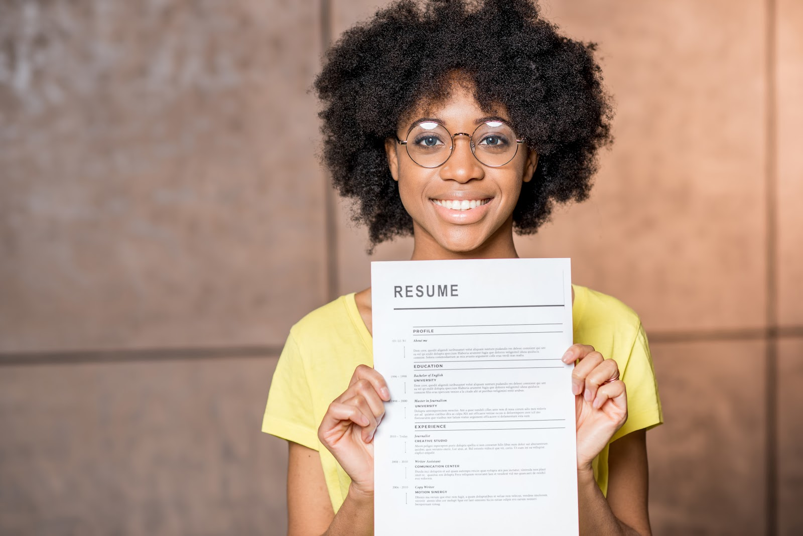 Jobs for recent college graduates: Woman holds resume up to camera