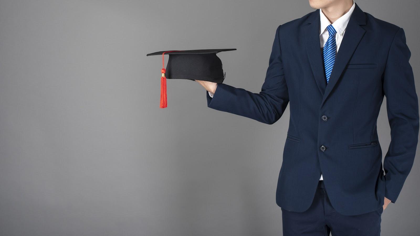 Jobs for recent college graduates: Man holds grad cap