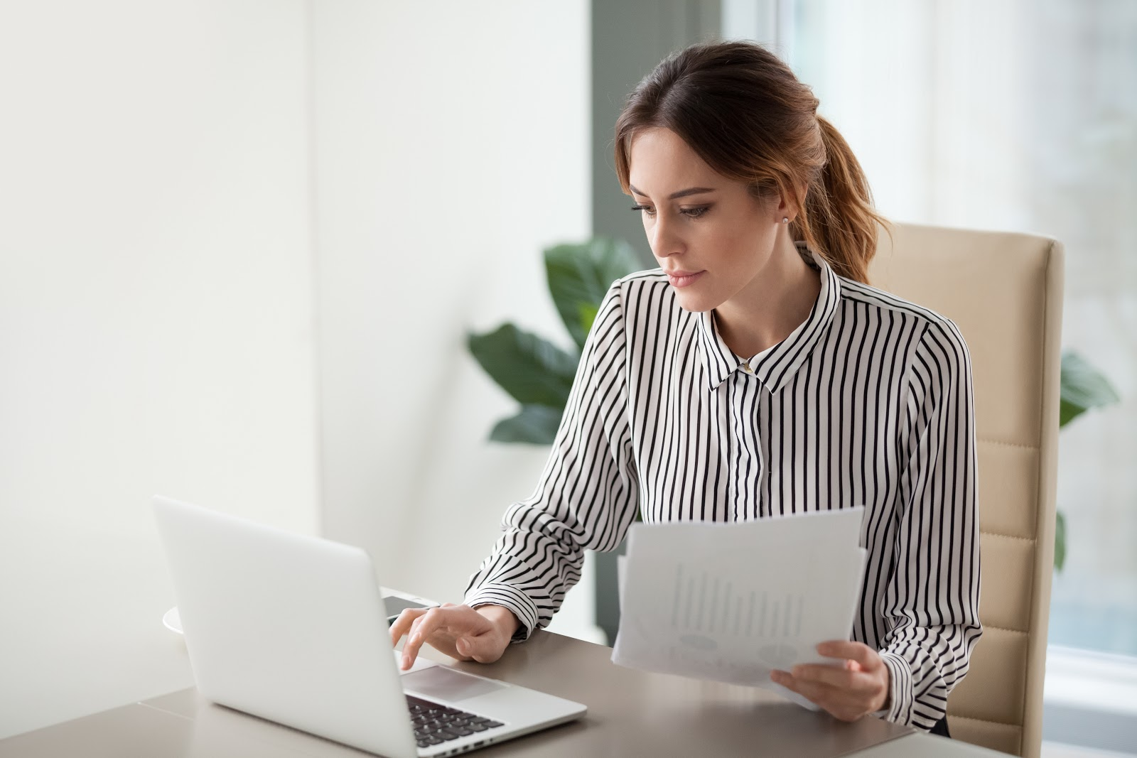 business analyst intern: woman working with her laptop and documents