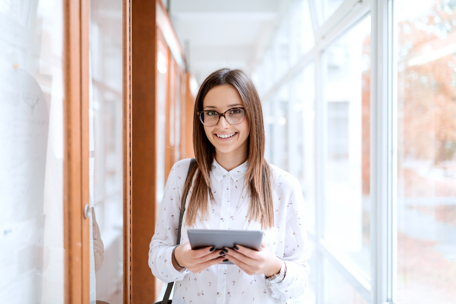 spring internships: College girl holding tablet while standing in hallway and looking at camera.