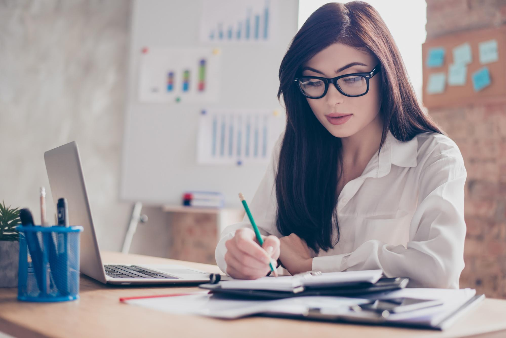 Woman with eyeglasses writing on her notebook organizer