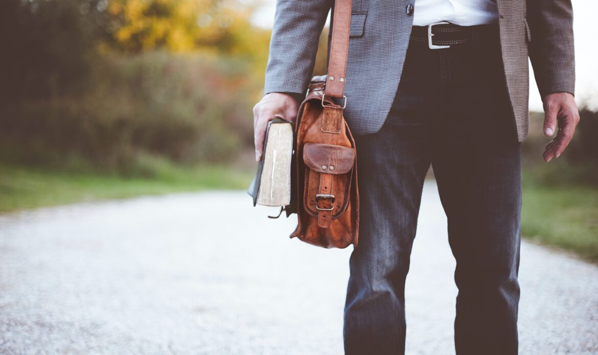 Man in a suit with a briefcase and a book.