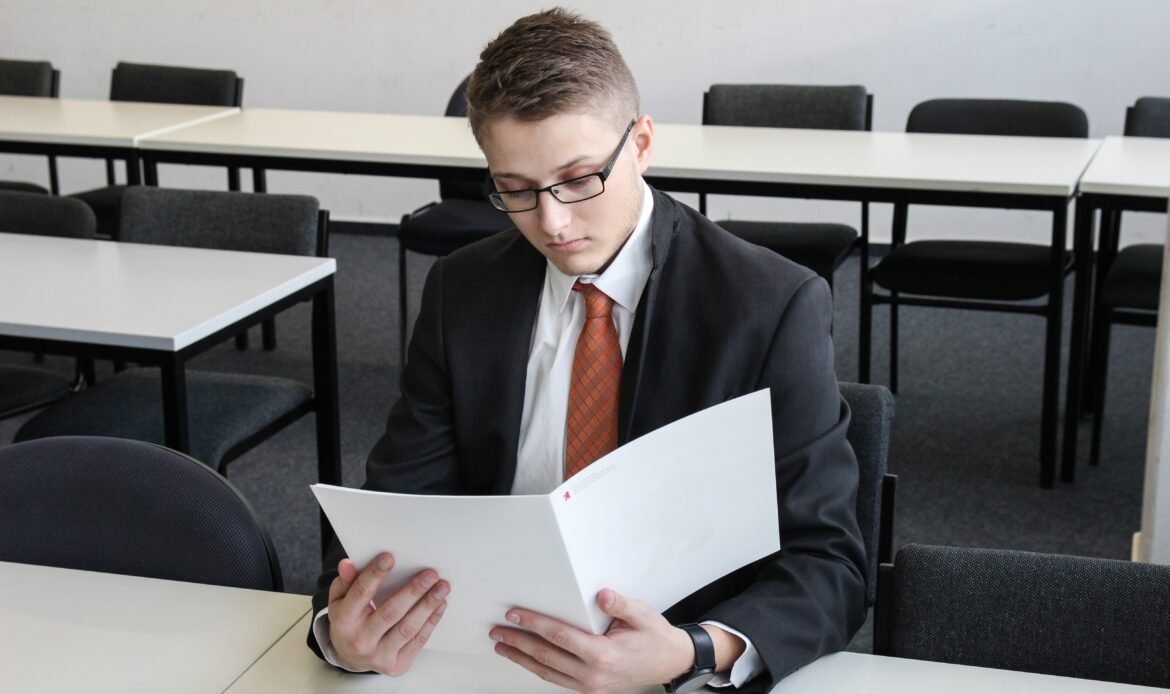 Man in a suit looking at a folder.