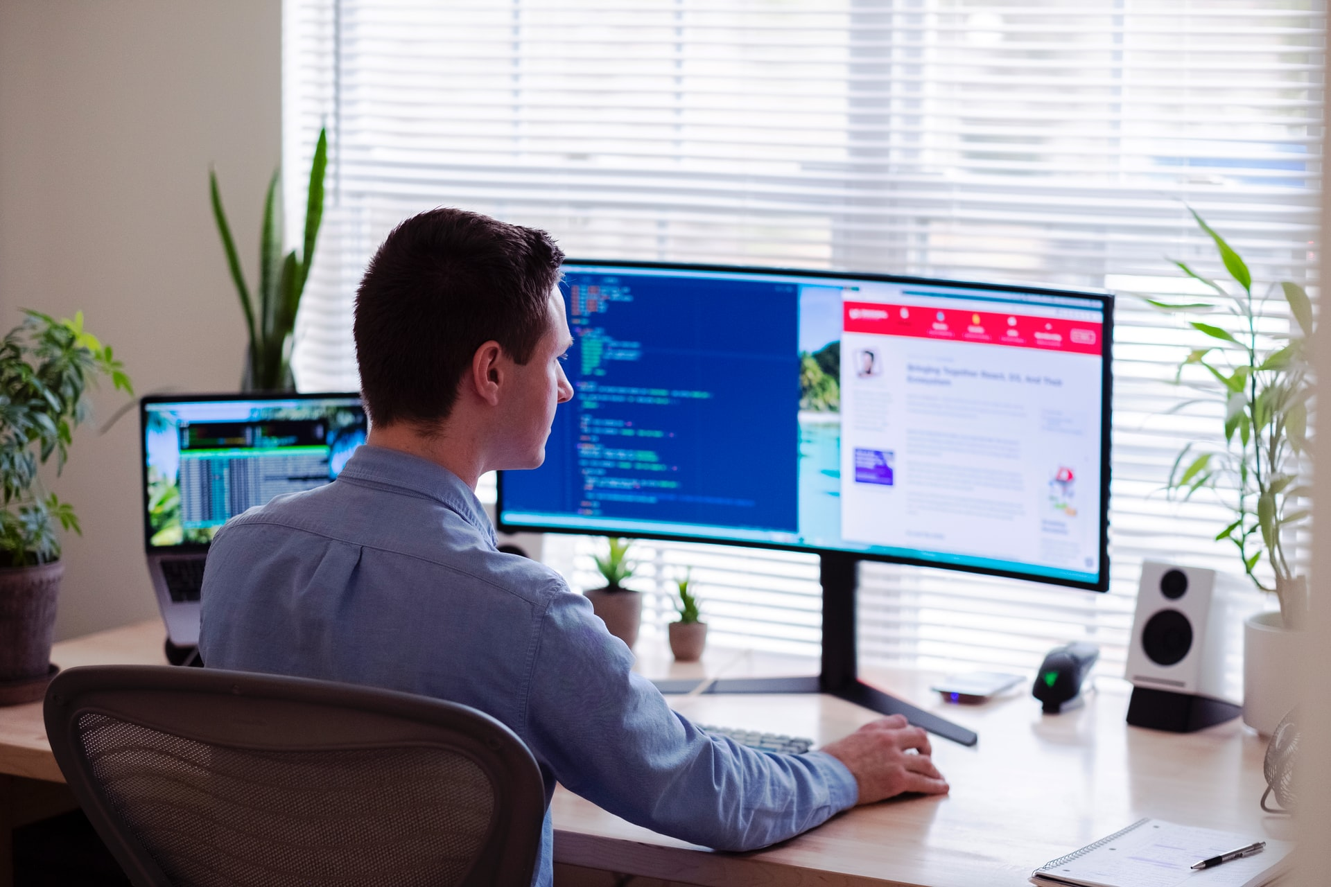 Man sitting at a desk with multiple monitors.