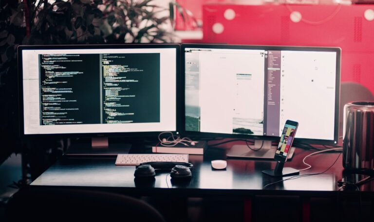 A technology set up of two monitors set on a desk with coding on one of them.