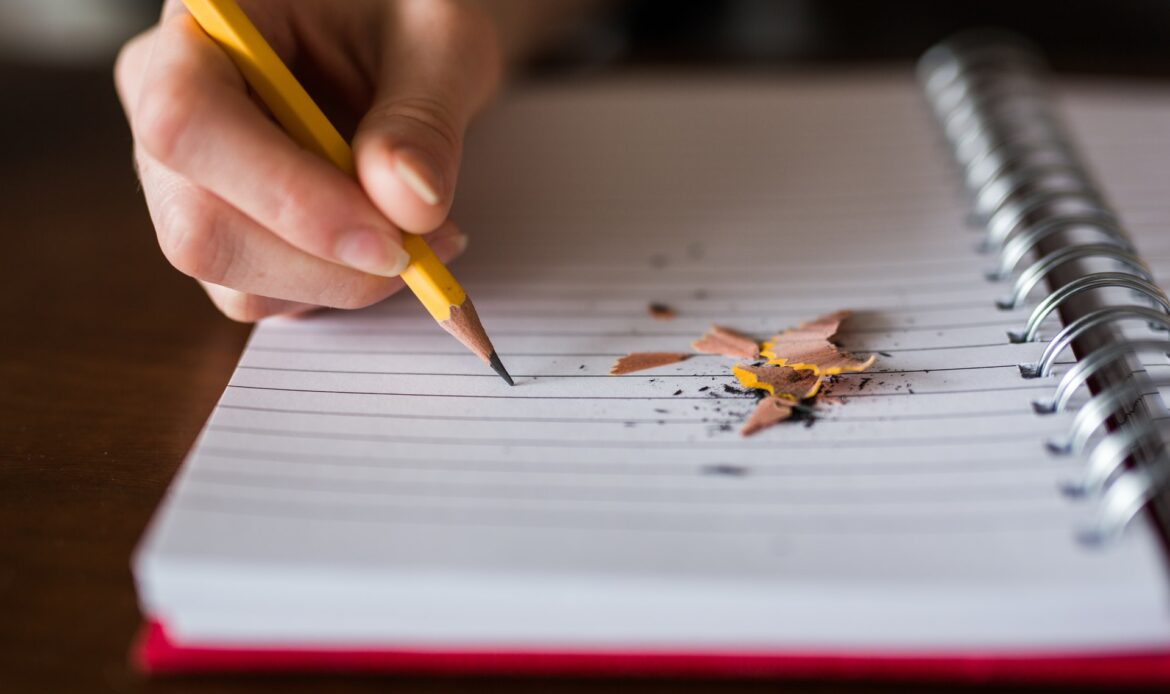 A hand holding a pencil to paper with shaving lying on the paper.
