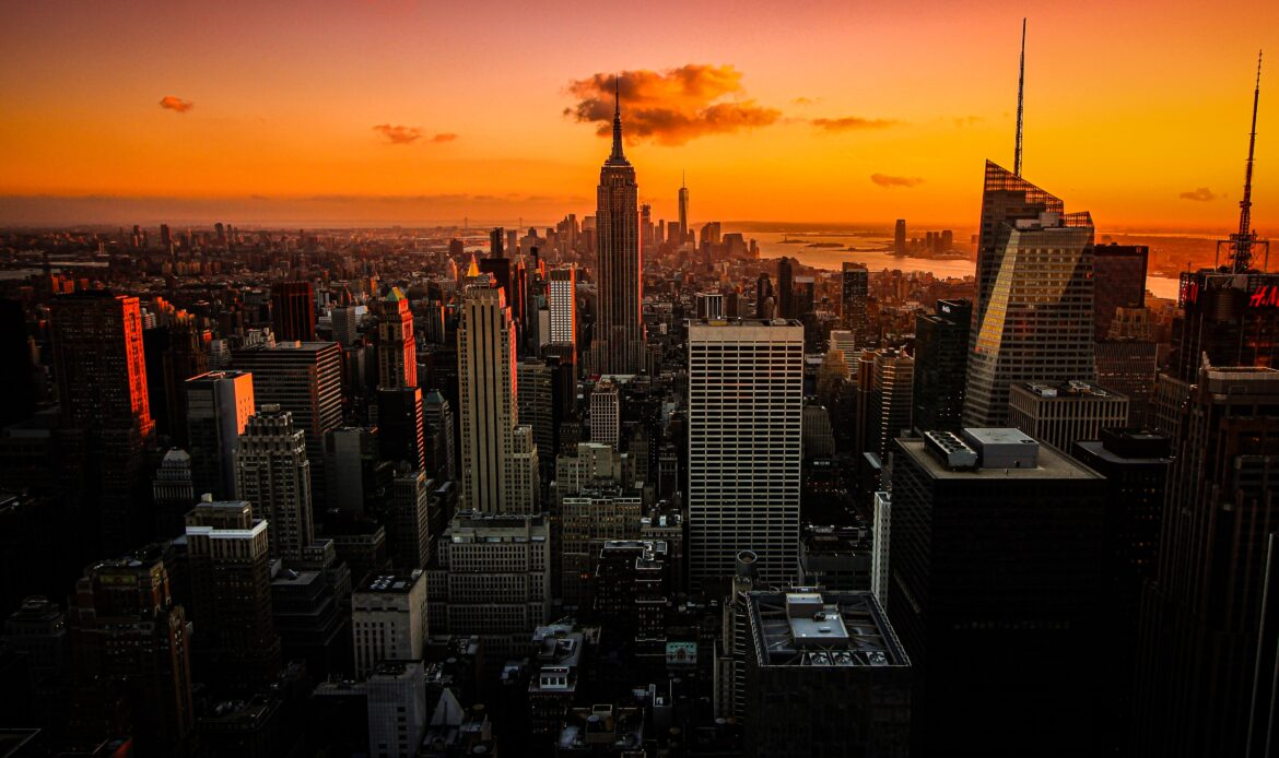 An orange sunset behind New York City
