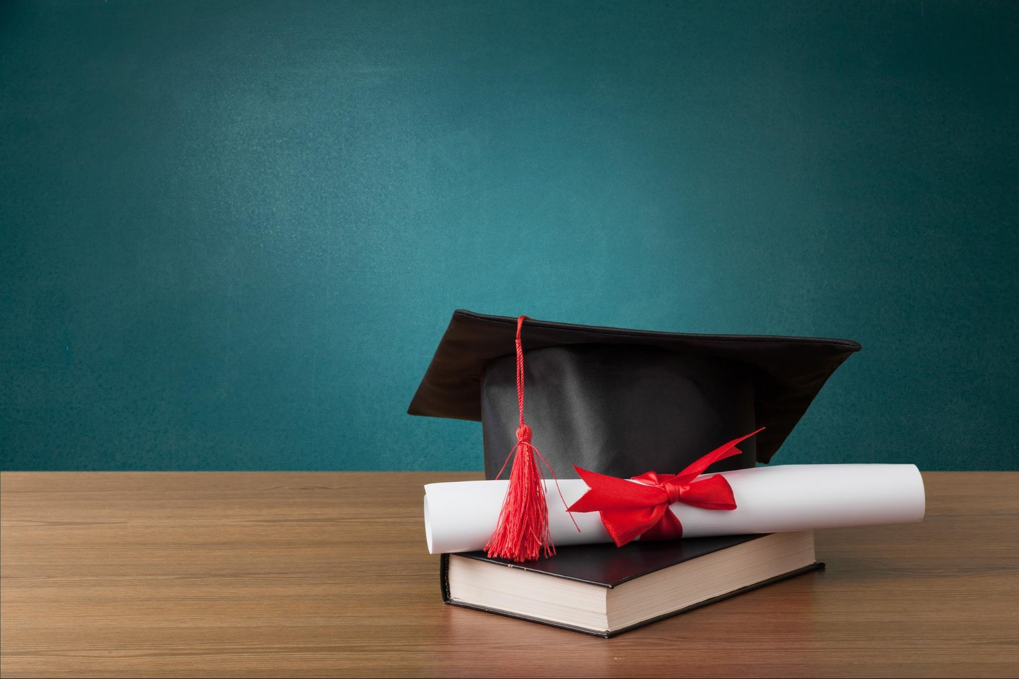 internships after graduation: Graduation cap, diploma and book on top of wooden table against a green background