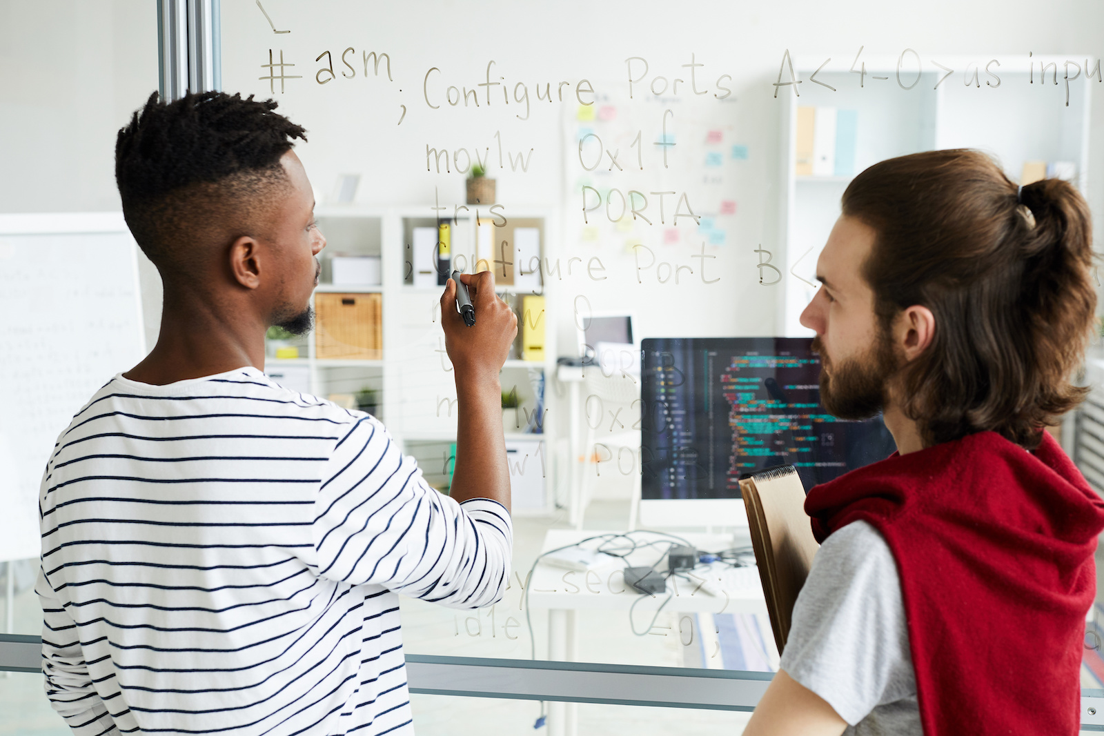 VMware internship: IT specialists discussing software language written on a transparent board