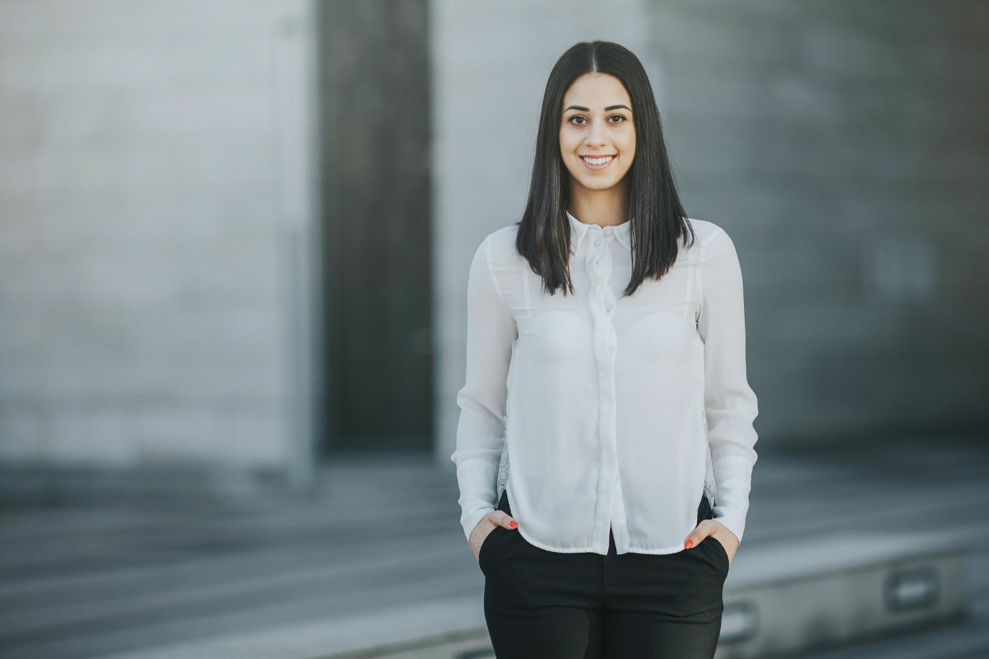 internships after graduation: Woman with her hands in her pockets and smiling at the camera