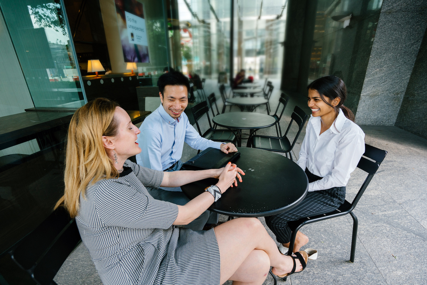 Three professionals talking outside a coffee shop