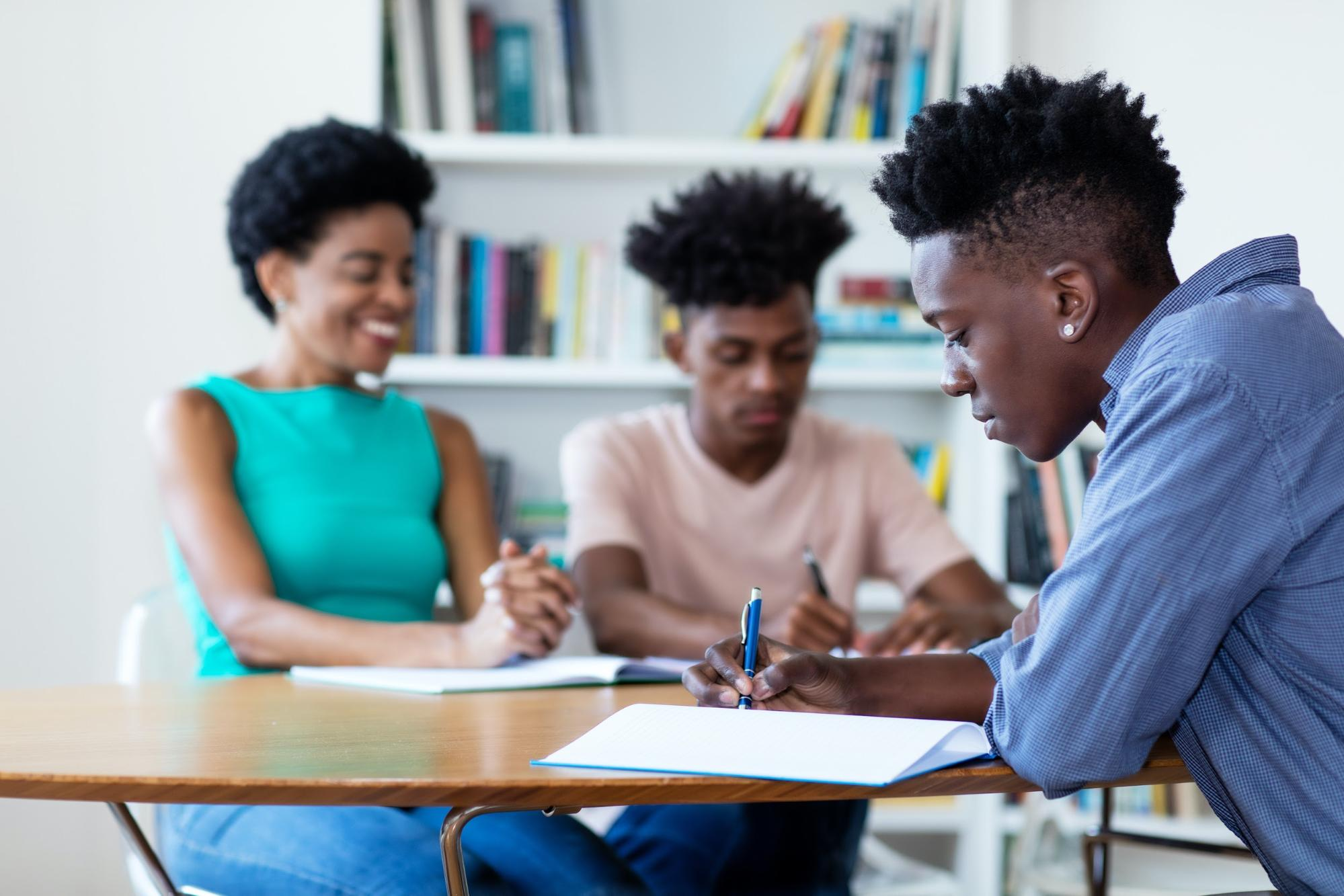 Teenage boy writing in his notebook as his female teacher looks over his classmate's work