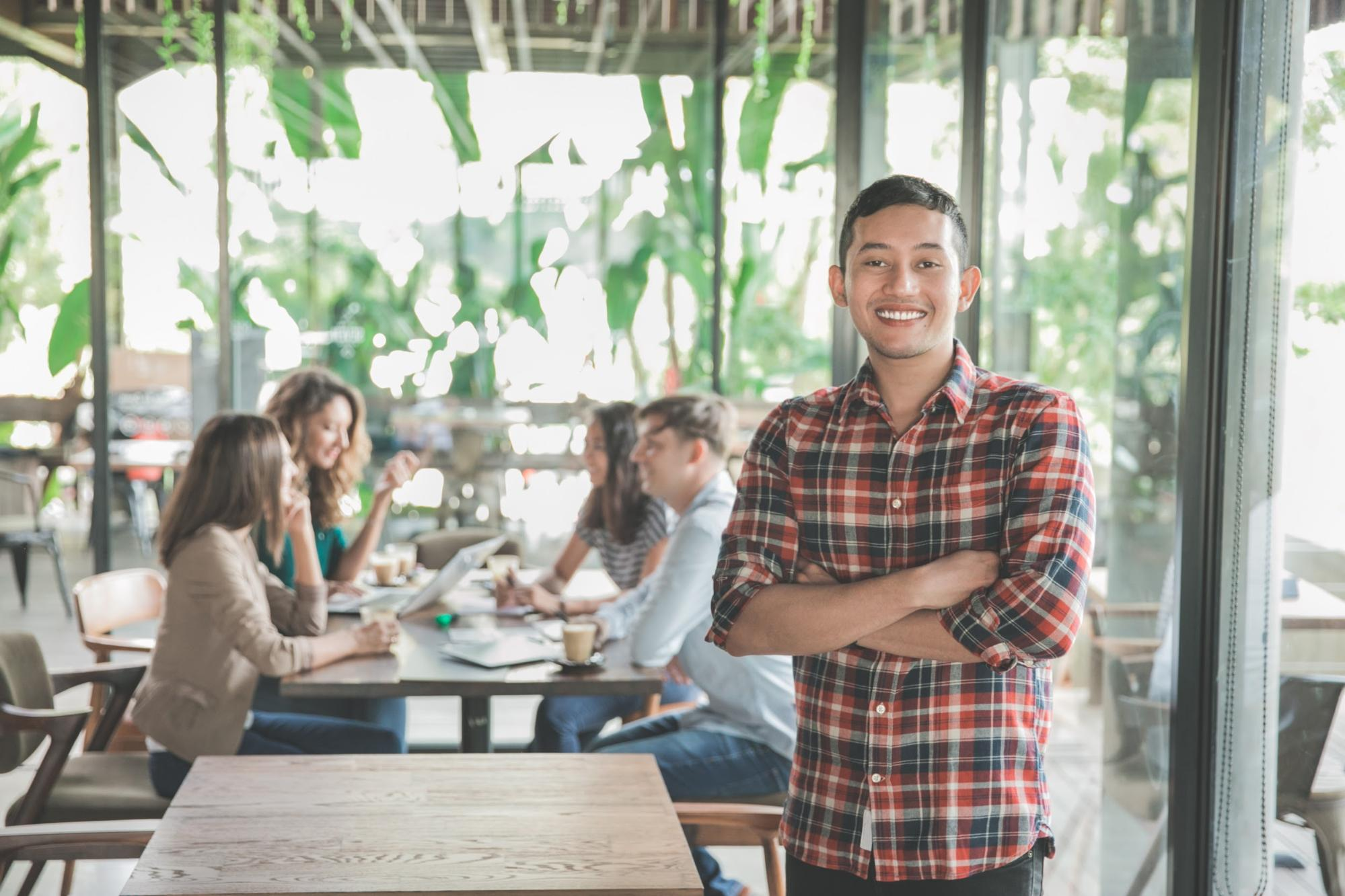 internships after graduation: Man smiling at the camera while his coworkers sit at a table behind him