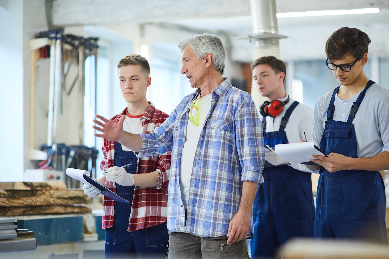Summer internship: Old man talking to young interns and taking down notes