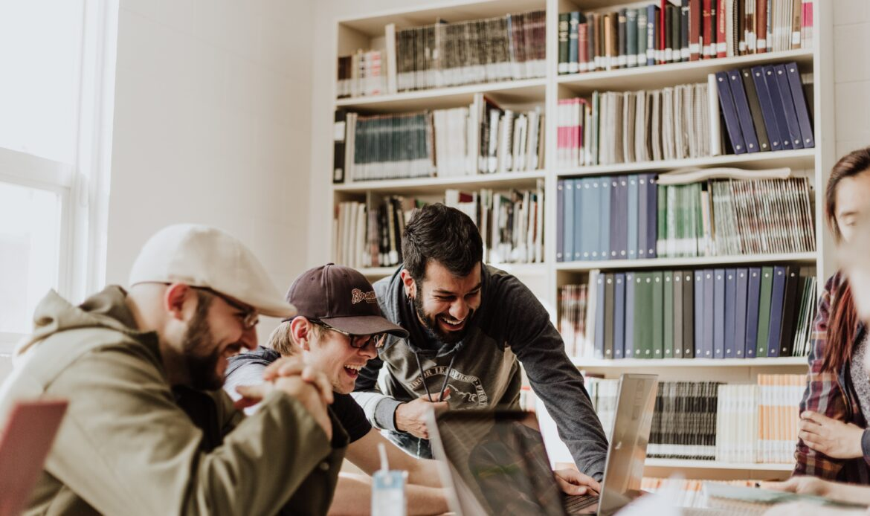Three men around a laptop laughing.