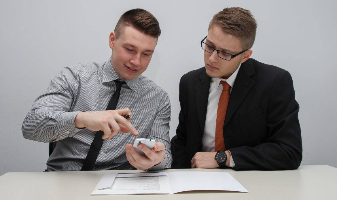 Two men in business professional sitting at a table and pointing at a mart phone