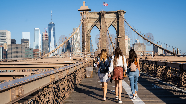 internships in NYC: three girls walking on the Brooklyn Bridge