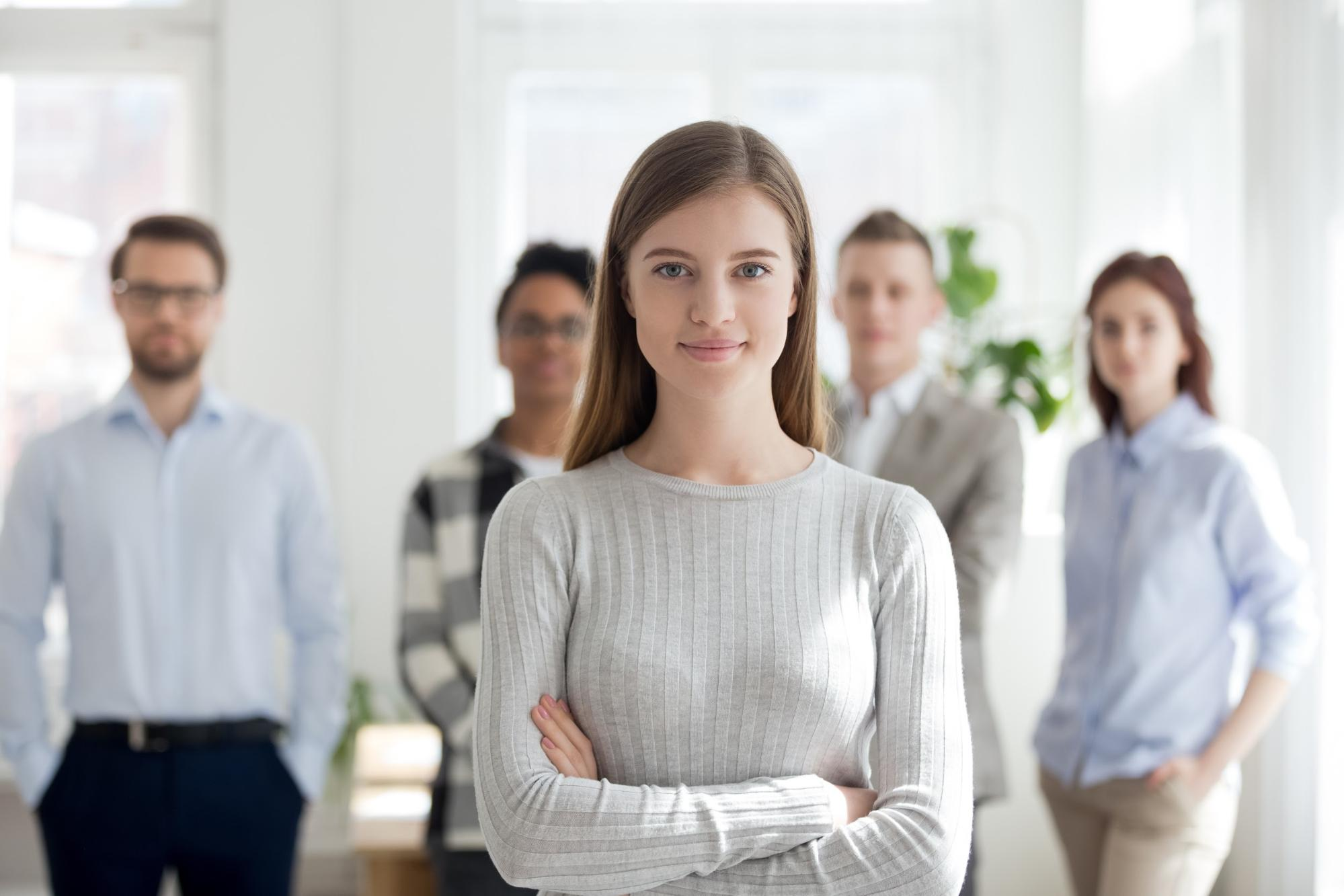 human resources jobs: Female looking at the camera and her team at the background