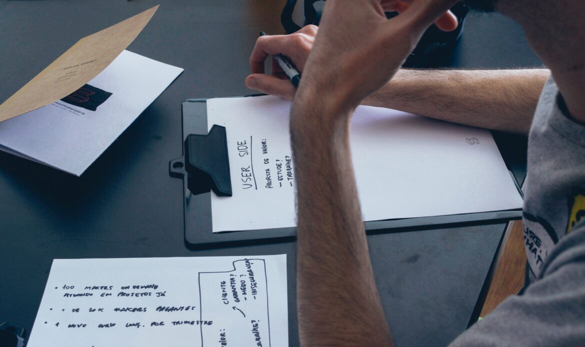 Man brainstorming about UX design on multiple papers.