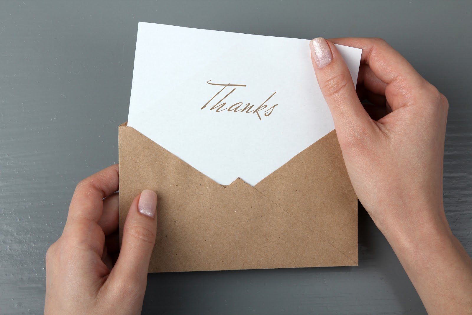 Woman's hands holding a thank you letter