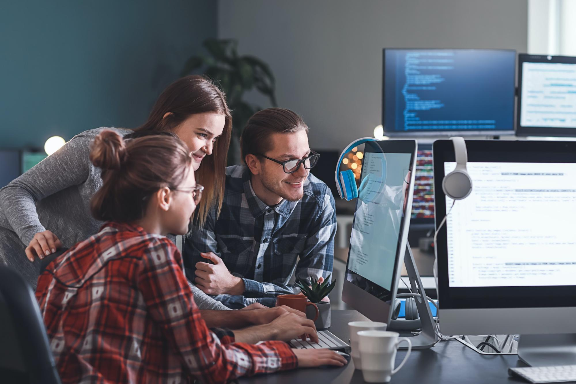 entry level IT jobs: two women and a man looking at the monitor