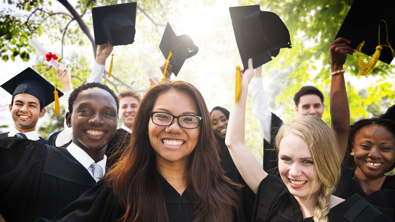 what to do with a business degree: students smiling and celebrating graduation