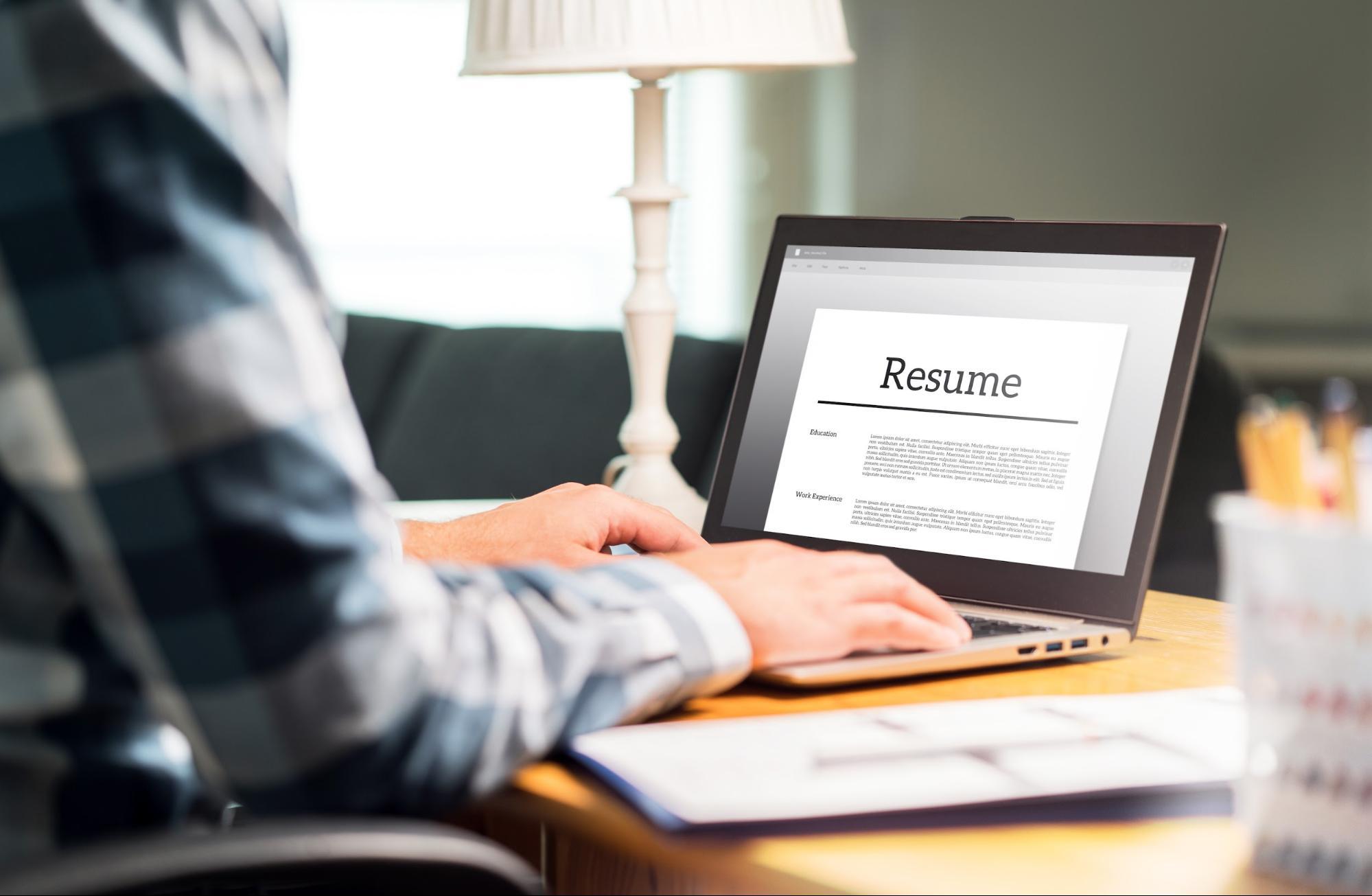 internship resume: Man updating his resume on his laptop