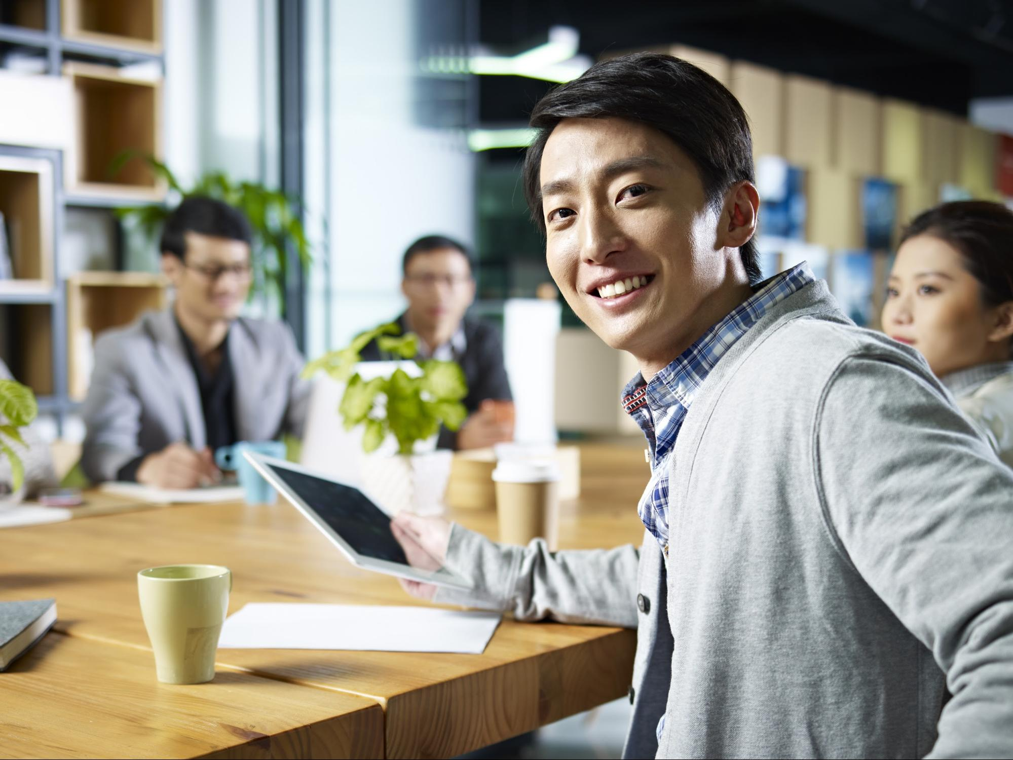 Fidelity internship: Businessman smiling at the camera while holding a tablet