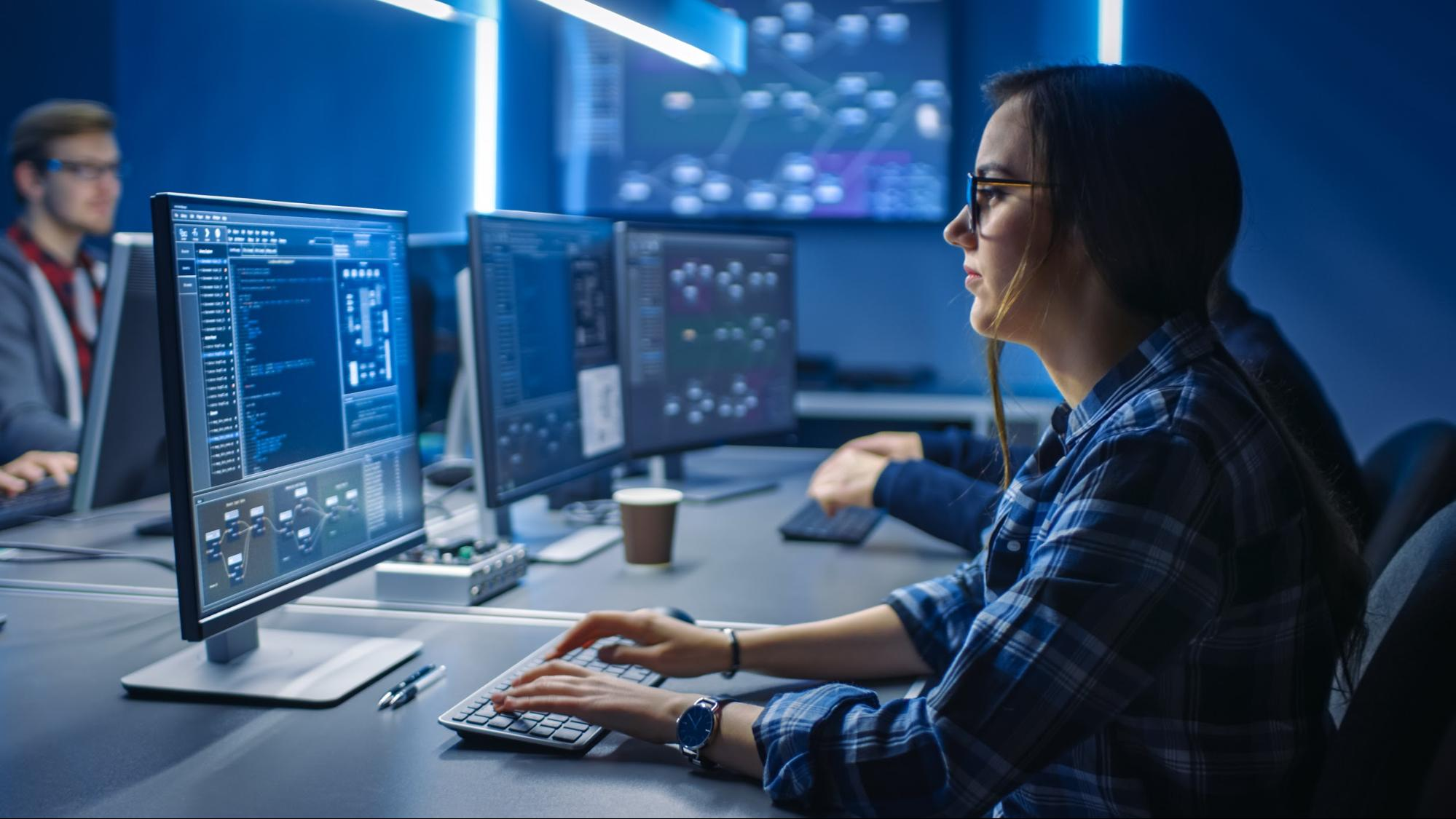 software developer internship: Female employee working on her desktop computer