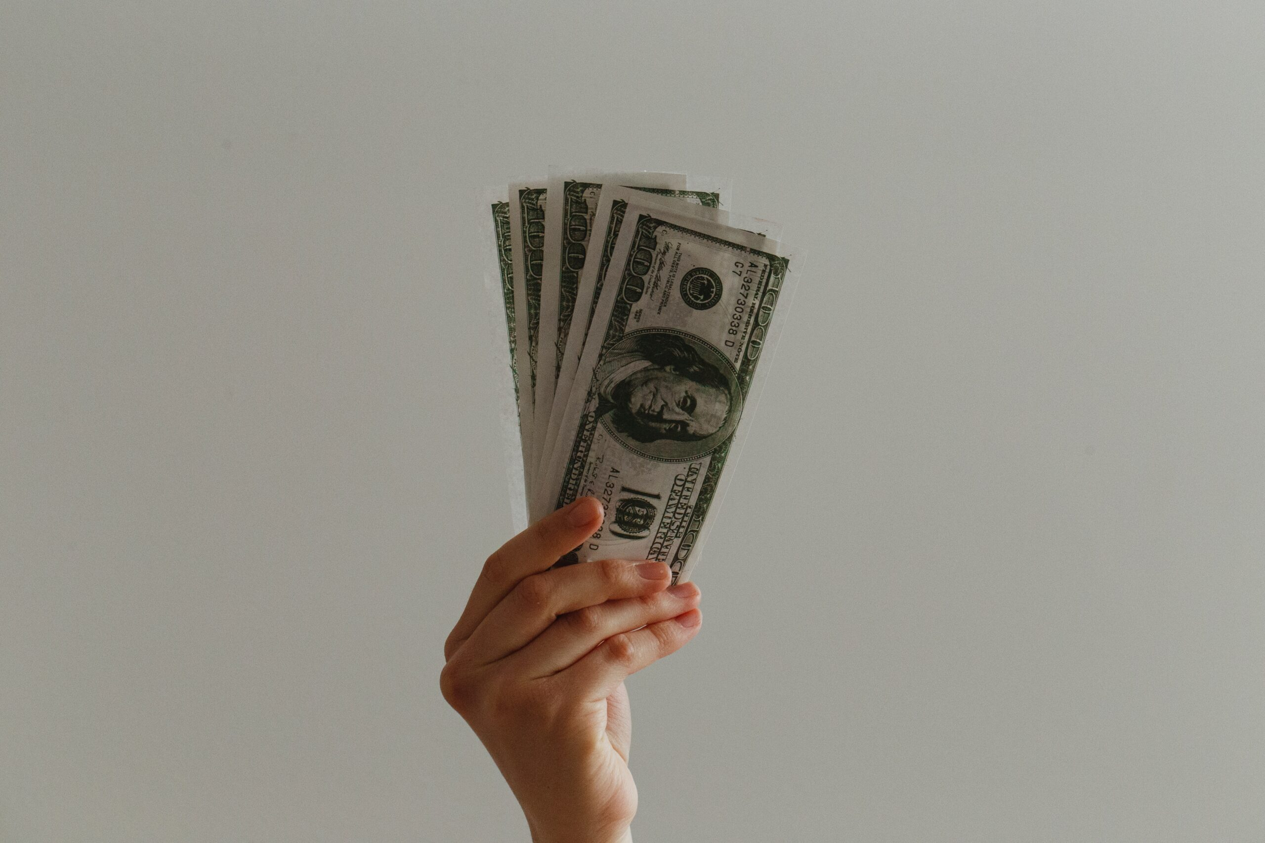 Hand holding five 10 dollar bills in the air with a white background