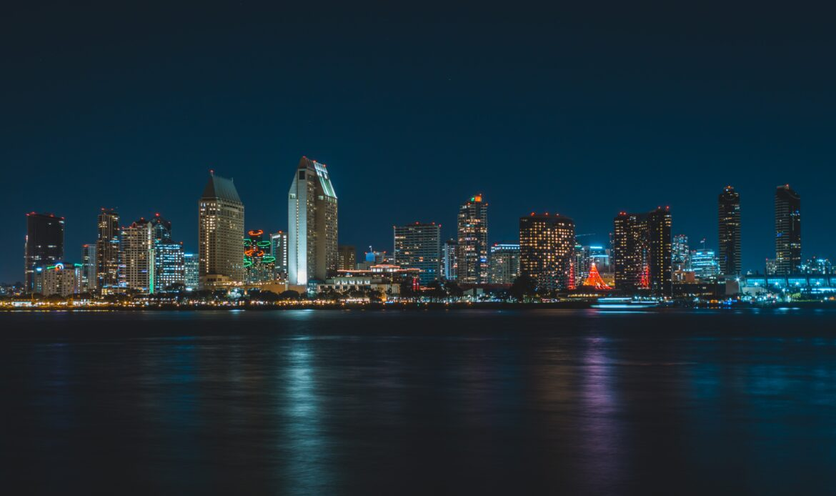 The Skyline of San Diego at night with the ocean in front.