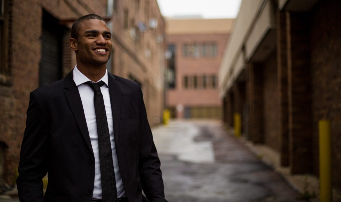 Man in a suit walking in an alley way smiling.