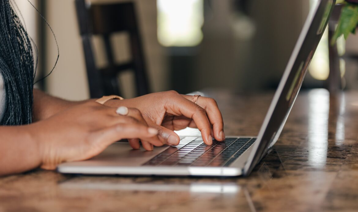 A woman typing on a keyboard of a laptop.