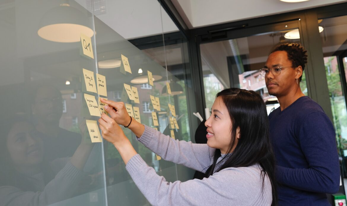 Two individuals working on planning out a product with sticky notes.