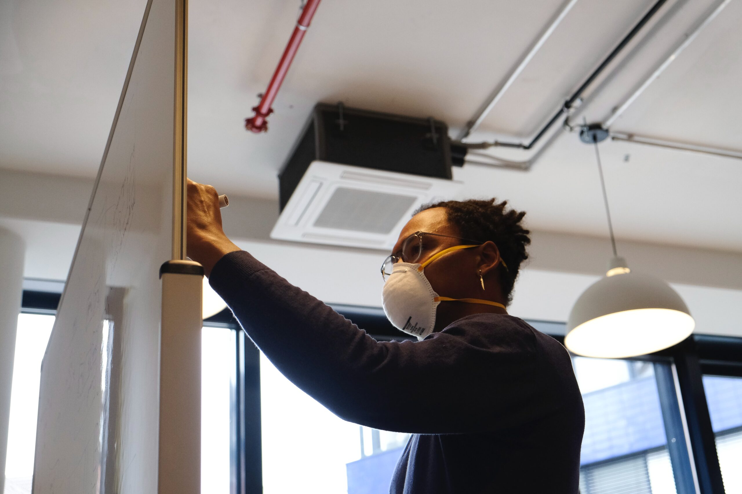 Product manager drafting ideas on a white board while wearing a mask in the office