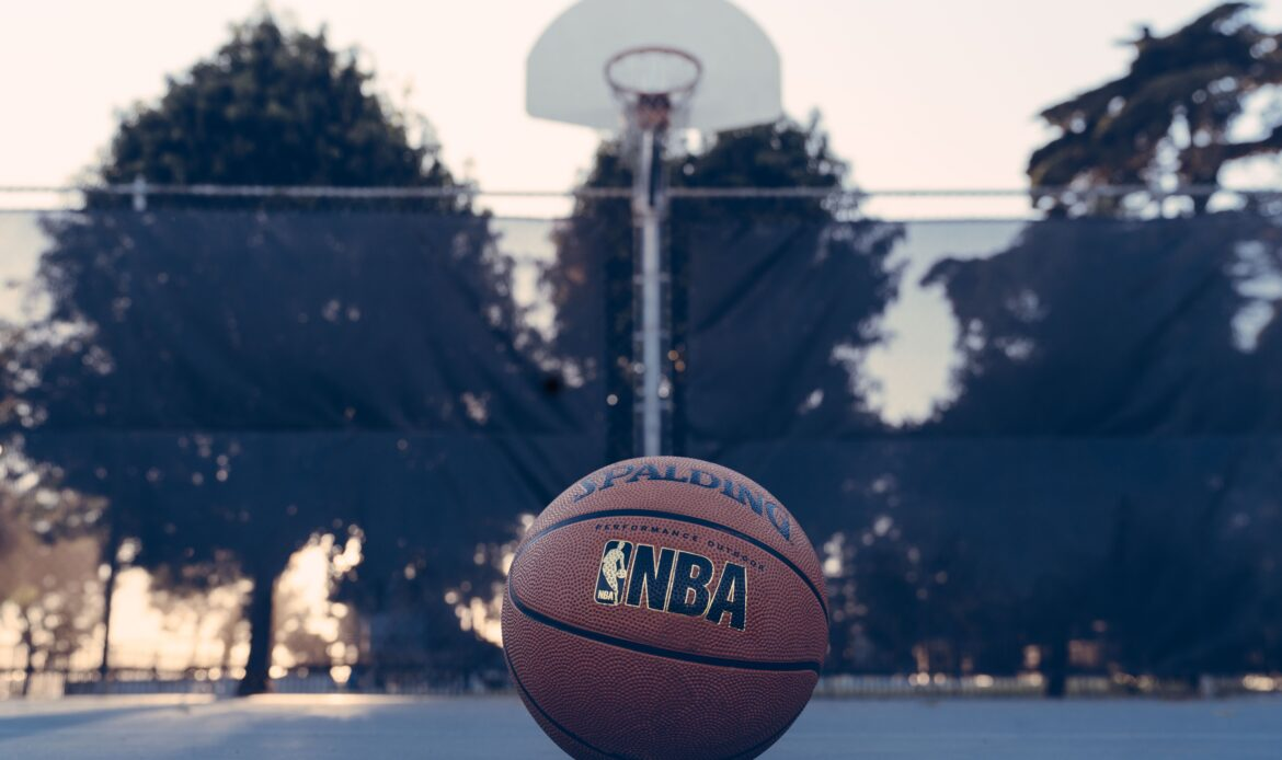 NBA basketball laying on an empty outdoor basketball court.