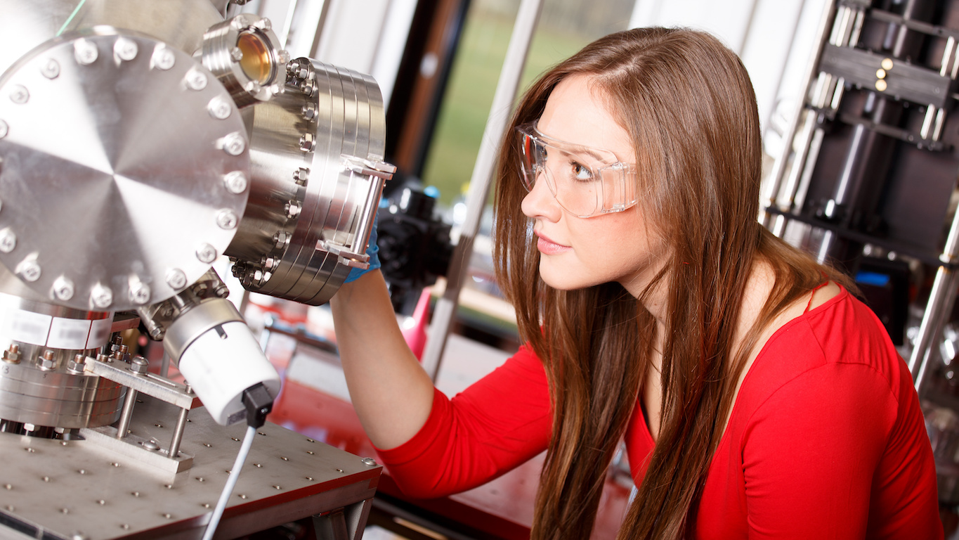 entry level jobs for physics majors: woman looking at the laser chamber