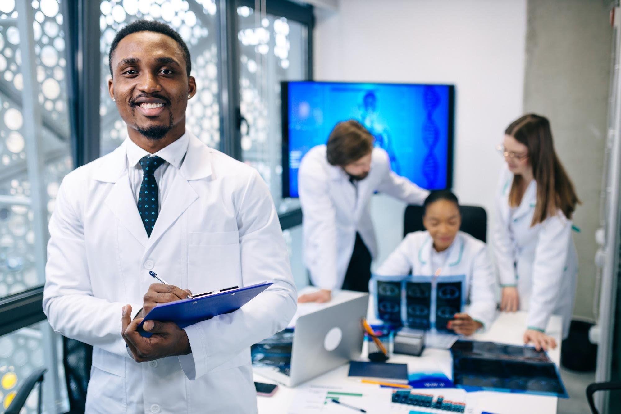 Man in lab coat standing in office with co-workers looking brain scans in background
