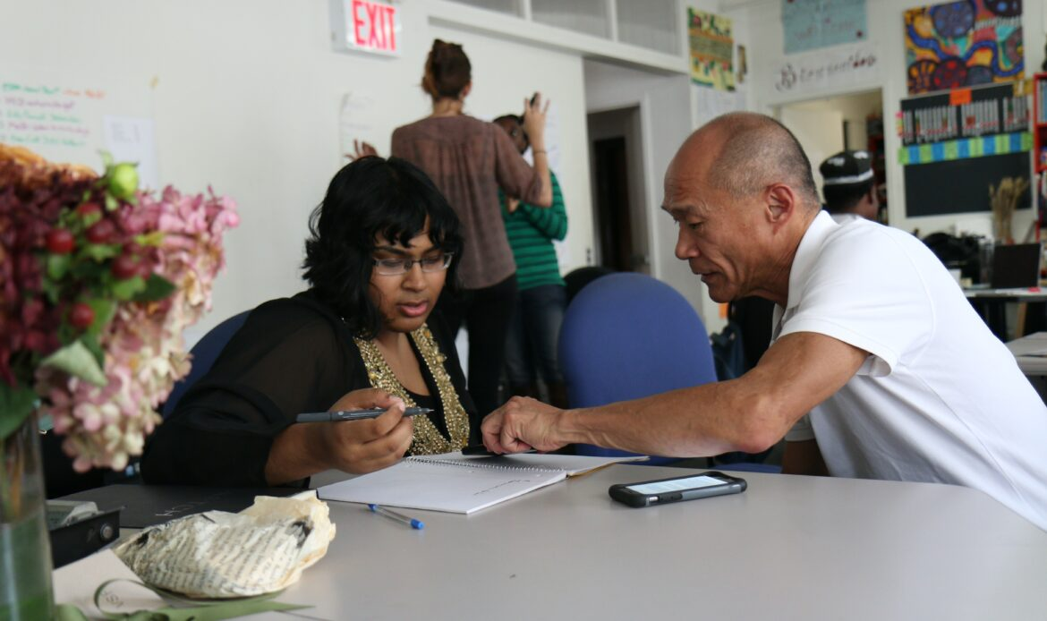 Two individuals working on a task together, the man is pointing to the woman's paper and she is holding a pen.