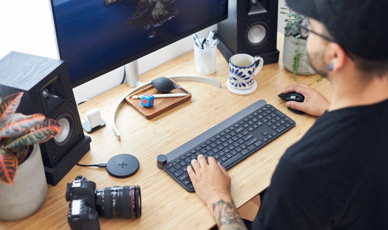 A man looking at a computer screen, at a desk.